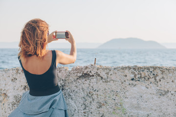 Young woman taking a photo using smartphone by the seaside