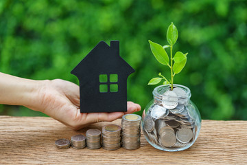growth sprout plant in jar with full of coins and hand holding paper house as property or mortgage investment concept