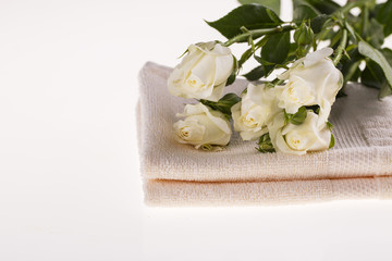 Spa. White roses and a towel on a white background