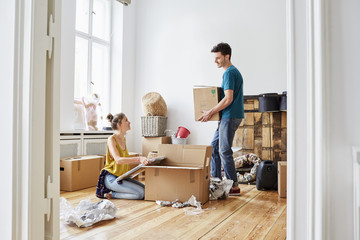 Couple Unpacking Cardboard Boxes At New Apartment