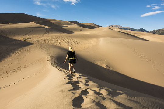 Young blonde woman walking on the Great Sand Dunes in Colorado