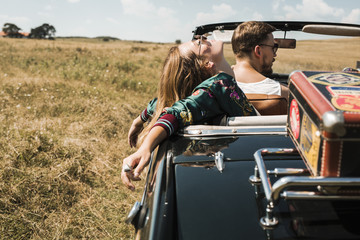 Couple Driving in Cabriolet in The Field