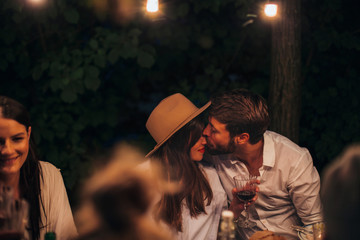 Group of friends enjoying together at a dinner party. A man kissing his wife