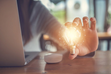 Closeup hand holding light bulb while using on laptop, New ideas innnovative technology and creativity.