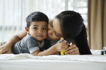 Woman kissing son lying on bed