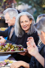 Group of friends enjoying a Farm To Table Dinner Party in backyard