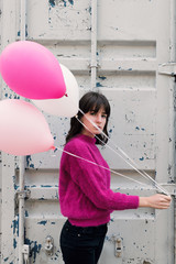 Calm girl with flying air balloons on metal background