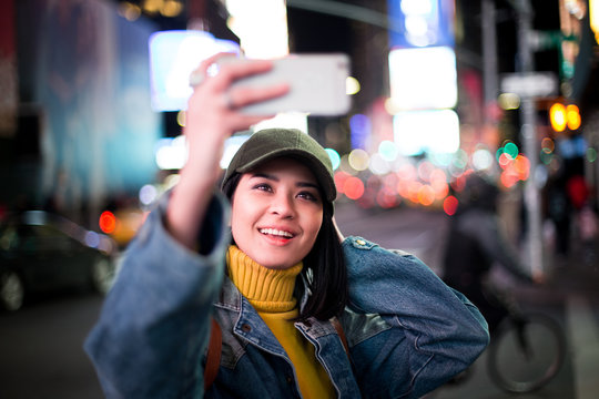 Female traveller taking a happy selfie in Times Square