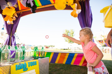 Young girl throws ring toss at county fair game