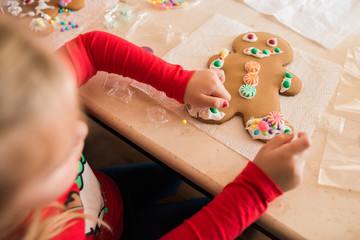 Young girl decorates gingerbread man cookie