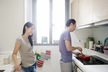 Husband cooking breakfast for his wife