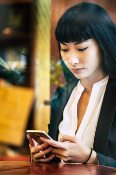 Businesswoman using smartphone while sitting in cafe