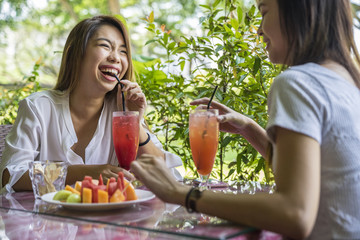 Two young ladies talking over cups of fruit juice and fruits.