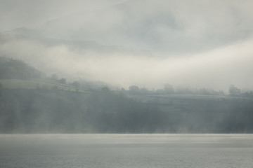 Thick fog over lake on an early morning