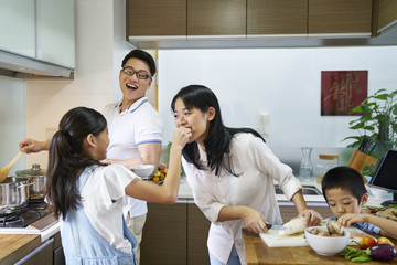 Family having a good time preparing food in the kitchen