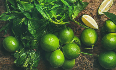 Flatlay of freshly picked organic limes and mint leaves for making cocktail or lemonade on wooden rustic board background, top view, horizontal composition, close-up
