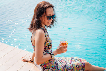 Chinese lady having a poolside drink