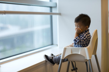 little boy thinking by the window Fotomurales