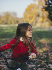 Cheerful child riding a bike in the park.