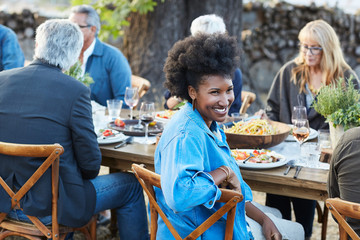 Portrait of African American woman with group of friends enjoying a Farm To Table Dinner Party in backyard