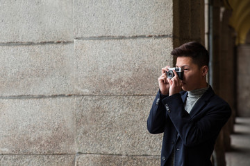 Casual young chinese man taking pictures in Madrid