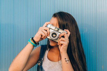 Teen Girl Taking Photos with Old Film Camera Against a Blue Wall