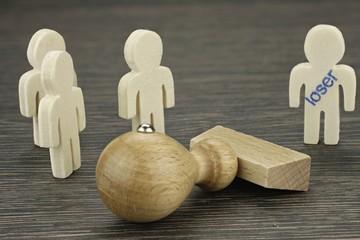 Ein Männchen wird als Versager gekennzeichnet und von der Gruppe ausgeschlossen – Darstellung der ungerechten Vorverurteilung einzelner durch die Gemeinschaft