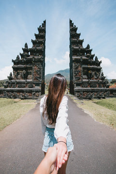 Back view of young lady holding her partner's hand in Bali