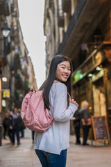 Chinese young woman in the streets of El Raval, in Barcelona. Smiling and holding a bag
