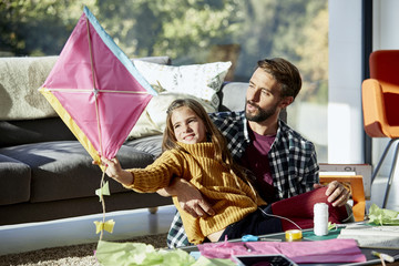 Father With Daughter Holding Kite At Home