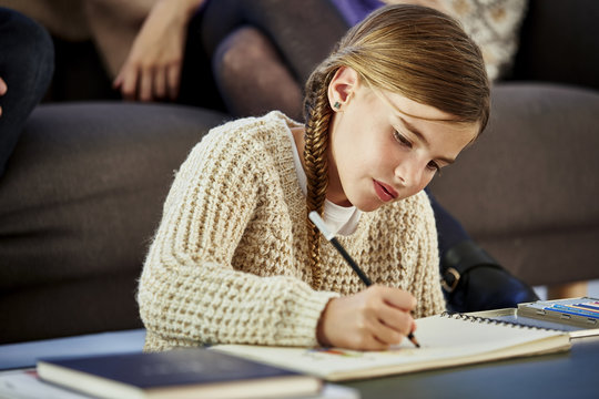 Girl Drawing In Coloring Book At Table