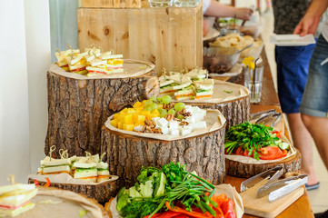 Outside Catering buffet table with a delicious food for guests of the event in rustic style. Service at business meeting, party, weddings. Selective focus, space for text