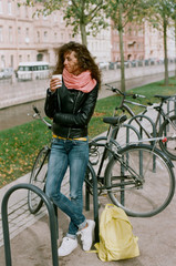 Woman having coffee at bicycle parking