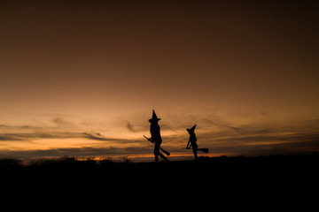 mother with daughter playing at halloween night