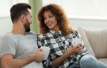 Beautiful couple holding a cup of drink while sitting on the cou