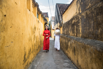 Vietnamese women in Ao Dai, traditional costume, and conical hat