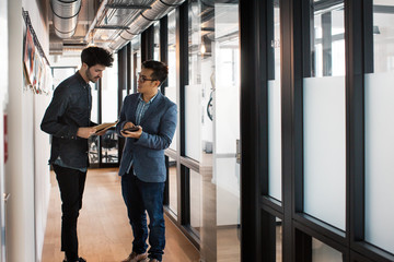 Two Young Businessmen Standing in Bright Modern Office Corridor