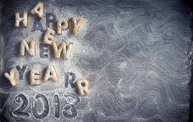 Happy New Year cookies on dark background with blank space