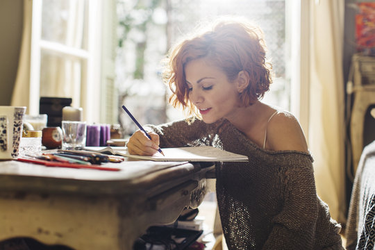 Woman drawing in adult coloring book with color pencils