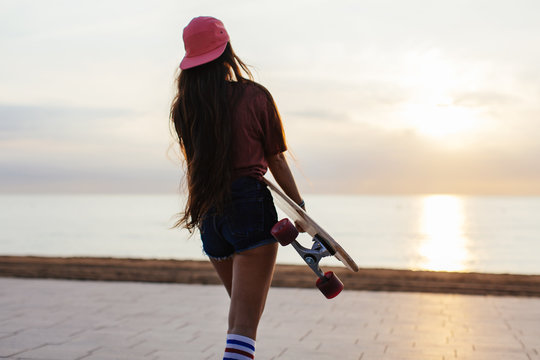 Girl holding her longboard walking by the beach at sunrise.