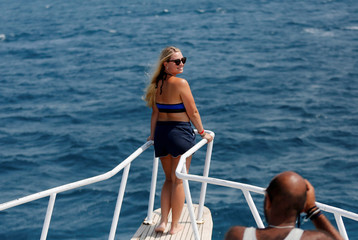 A tourist takes a photo while on the Red Sea during summer holidays near the resort of Hurghada