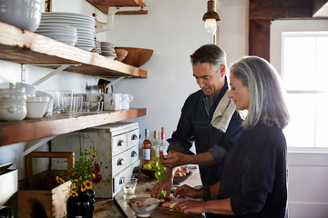 Mature couple cooking in rustic farmhouse kitchen