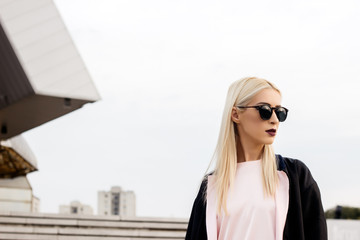 Portrait of a beautiful alternative blonde female model with sunglasses on the street