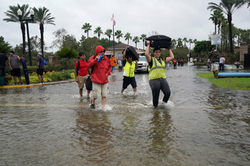 Volunteers carry the luggage of those evacuated by boat from the Hurricane Harvey floodwaters in Houston