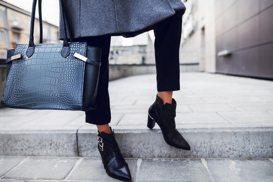 Elegant outfit. Close up of textured big dark blue bag. Model posing in street, wearing short trousers, black pointed toe ankle boots. Female fashion concept. Copy, empty space for text