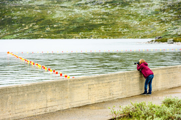 Young adult woman taking photo of safety buoys along a rope in the water by a small dam. Mountain landscape in background.