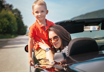 Mother and little son sitting in cabriolet car