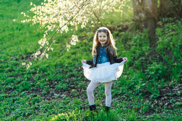 Cute smiling little girl in white skirt and denim shirt on the nature background
