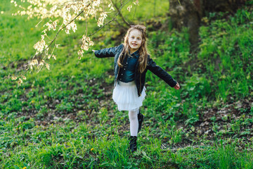 trendy emotional little girl in black boots. Funny girl with open mouth looking at camera