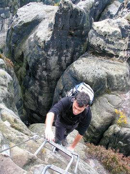 Mann klettert Krampen am Felsen hoch in der Sächsischen Schweiz, Deutschland